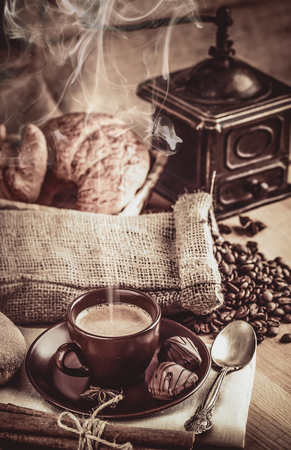 bracing: Cup fragrant hot coffee with bean chocolate sweet and croissant in vintage rustic style cinnamon steam smoke on wooden board for bracing morning breakfast.