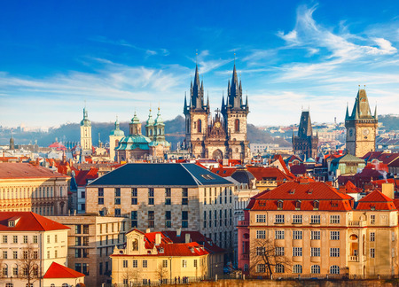 High spires towers of Tyn church in Prague city (Church of Our Lady before tyn cathedral) urban landscape panorama with red roofs of houses in old town and blue sky with clouds