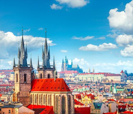 broach: High spires towers of Tyn church in Prague city (Church of Our Lady before Tyn cathedral) urban landscape panorama with red roofs of houses in old town and blue sky with clouds Stock Photo