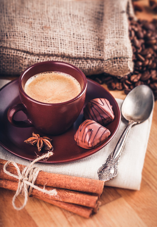 bracing: Cup fragrant hot coffee with bean chocolate sweet and loaf in vintage rustic style on wooden board for bracing morning breakfast