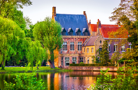 crone: Vintage building over lake of love in Minnewater park in Bruges Belgium near Beguinage monastery of Beguines. Picturesque landscape with green trees sunset time.