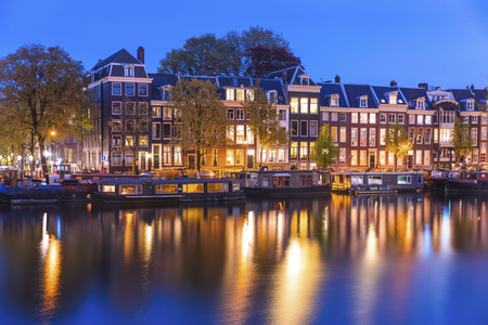 water town: Evening town Amsterdam in Netherlands on bank river canal Amstel with shining window. Panorama landscape brown house over water reflection. Stock Photo