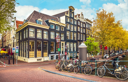 crone: Urban landscape in Amsterdam Netherlands. Panorama street with bicycle tree and road traditional Dutch architecture.