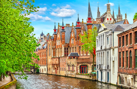 Medieval town Bruges in Belgium. Panorama and landscape vintage channel with old brick house broach on roof. Spring sunny day blue sky white cloud end green trees. Stock Photo