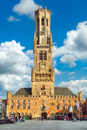 Market Square (Markt) in Bruges, Belgium. View to Belfort tower building in historical centre Brugge of old town. Day panorama with blue sky and clouds.