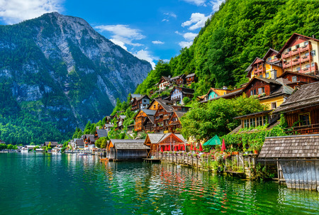 locality: Hallstatt old town houses on hill Austria on lake Hallstattersee among green forest mountains Austrian Alps.
