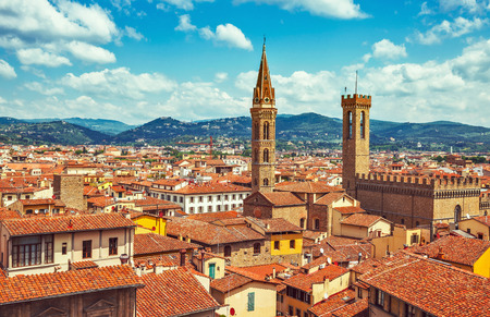 locality: Panorama view to tiled roofs and towers of Town hall in Florence old town in Italy. Blue sky with clouds knolls horizon.