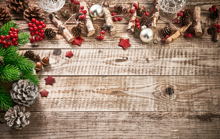 Christmas card with firtree pinecone and glass balls on old wooden board in rustic style copyspace. Stock Photo