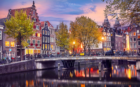 Red-light district in Amsterdam city picturesque landscape panorama evening town with pink sunset sky. Bridge over canal river Amstel.
