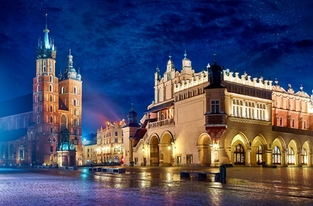 Saint Mary's Basilica in Krakow Poland with Cloth Hall at main square stone paving stones picturesque landscape nighttime city blue sky and stars. 版權商用圖片