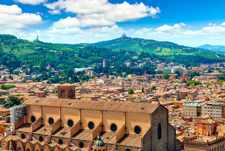 Bologna, Italy. Top view to Basilica of San Petronio and tegular roofs of houses of old town. Landscape panorama with scenic green knolls and blue sky with clouds on skyline.