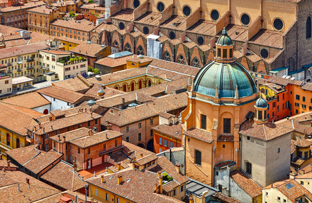 Bologna, Italy. Top view to dome of medieval ancient cathedral Sanctuary of Santa Maria della Vita. Terracotta houses with tiled roofs. Sunny day.