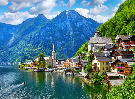 Hallstatt, Austria. View to Hallstattersee Lake and Alps mountains summits. Ancient houses at lake banks with chapel. Summer day. Blue sky with clouds.