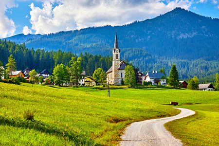 Austria. Traditional church with chapel in village among picturesque landscapes in austrian Alps mountains. Summer green lawns and fields. Knolls covered with forests and trees. Blue sky with clouds. Imagens