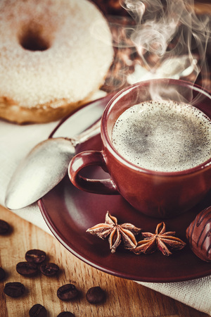 Cup fragrant hot coffee with bean chocolate sweet and loaf in vintage rustic style