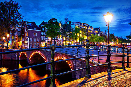 Amsterdam, Netherlands. Bridges with nighttime illumination over canals with water in Old town. Quarter with traditional dutch houses.