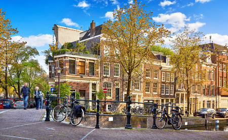 Street of Amsterdam city. Netherlands. Bridge over channel with traditional dutch houses and bicycles. Imagens