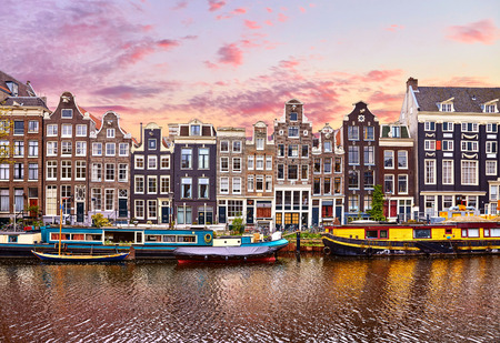 Amsterdam, Netherlands. Floating Houses and houseboats and boats at channels by banks. Banco de Imagens