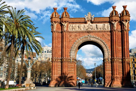 Triumphal Arch in Barcelona, Catalonia, Spain. Arc de Triomf at boulevard street. Alley with tropical palm trees.