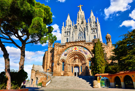Barcelona, Spain. Tibidabo Cathedral. Temple of the Sacred Heart of Jesus at Mount Tibidabo. High pine-tree tree and blue sky with cloud of summer day. Famous landmark in Catalonia, Espana.