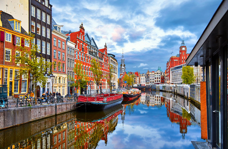Channel in Amsterdam Netherlands houses river Amstel landmark old european city spring landscape. Imagens