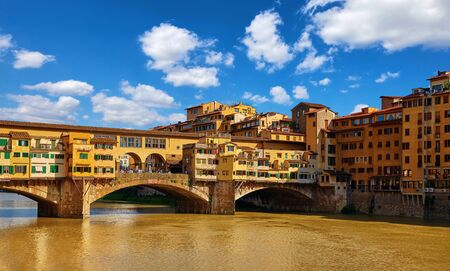 Panorama view to ancient bridge Ponte Vecchio at river Arno in Florence old town, famous touristic place of Tuscany region, Italy. Imagens