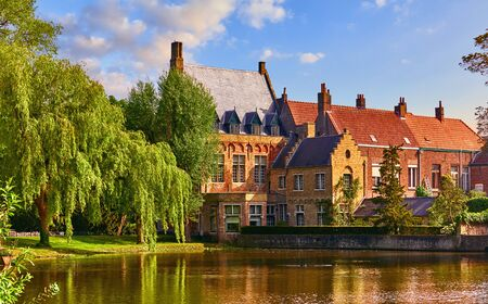 Vintage building over lake of love in Minnewater park in Bruges Belgium near Beguinage monastery of Beguines. Stockfoto - 128002028