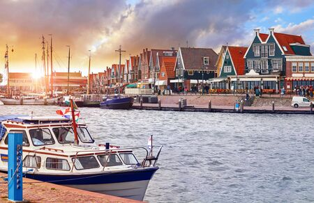 Volendam, Netherlands. Luxury yacht parked by pier in bay of North Sea on evening sunset under traditional old town. Stockfoto - 128001836