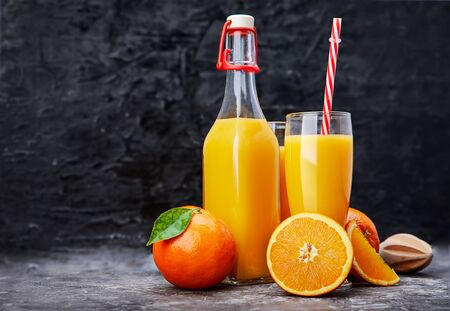 Freshly squeezed orange juice in glass bottle with straw. Fruity still life on black backdrop and grey concrete surface rustic style. Stockfoto