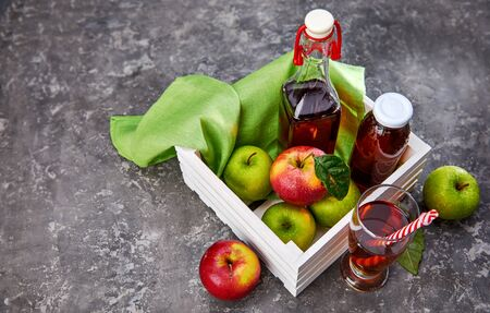 Apple juice in glass bottle and cup with green and red apples at gray concrete surface in rustic style. Stockfoto