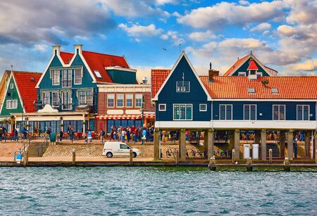 Volendam, Netherlands. Small town fishing village in North Holland near Amsterdam with traditional Houses with Red Tegular Roofs at Waterfront with Docks by Sea.