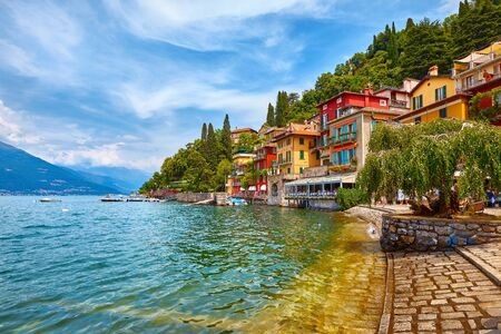 Varenna, Italy. Picturesque town at lake Como. Colourful motley Mediterranean houses at stone beach coastline among green trees.