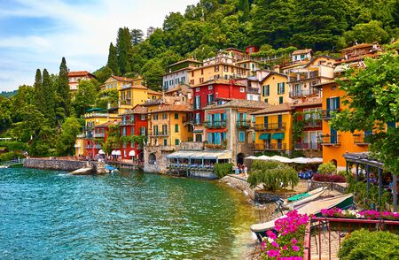 Varenna, Italy. Picturesque town at lake Como. Colourful motley Mediterranean houses on knoll by coastline among green trees.