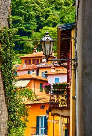 Varenna, Italy. Vintage street lamp at narrow street between buildings of old Mediterranean town at lake Como in Lombardy region. Stockfoto