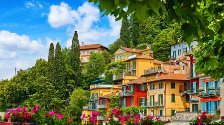 Varenna, Italy. Picturesque town at lake Como. Colourful motley Mediterranean houses on knoll by coastline among green trees. Stockfoto - 129272150