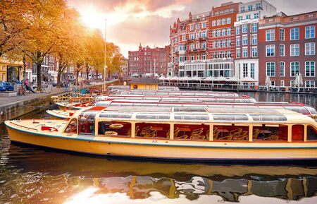 Amsterdam, Holland, Netherlands. Amstel river, canals and boats against evening dusk sunset sky cityscape.