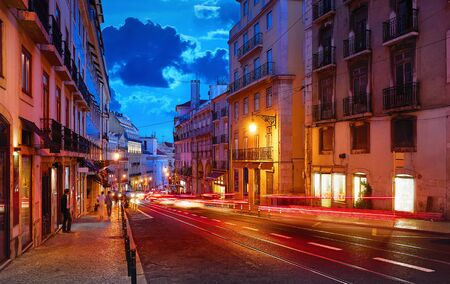 Porto, Portugal. Nighttime city life. Old town street with evening illumination and sky with clouds blue hour.