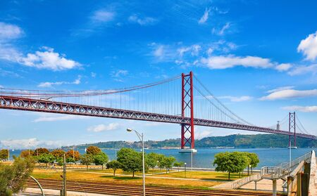25th April Bridge in Lisbon, Portugal. Famous landmark on river Tagus. Summer sunny landscape with blue sky.