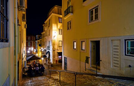 Lisbon, Portugal. Nighttime streets with stone stairs and restaurants under street lamps with evening illumination.