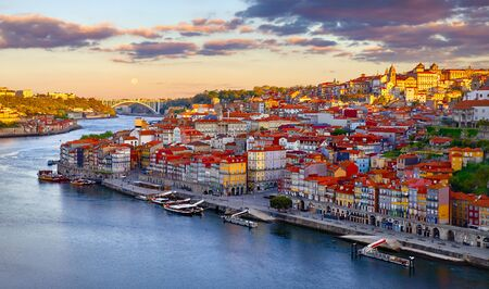 Antique town Porto, Portugal. Sunset sun over silhouettes skyline of roofs of houses along river. Stockfoto