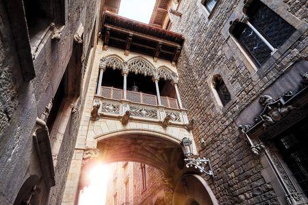 Antique Bridge between stone walls of medieval buildings in in old town.