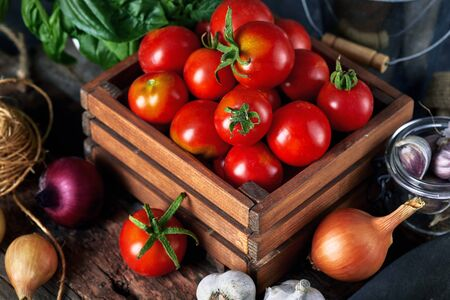 Harvest tomatoes in wooden box spicy herbs and spice at old board in rustic style. Stockfoto - 130832221