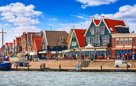 Small town fishing village in North Holland near Amsterdam with traditional Houses with Red Tegular Roofs at Waterfront with Docks by Sea.