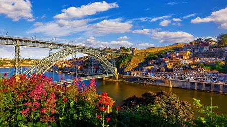 Porto, Portugal. Evening sunset picturesque view at old town with antique houses and red roofs near bridge Ponte de Dom Luis on river Douro. Standard-Bild