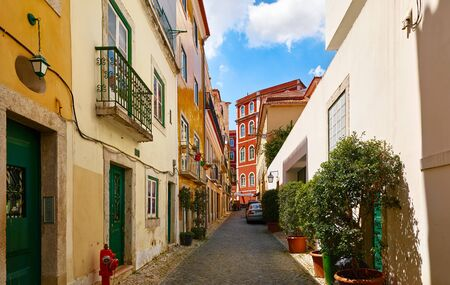 Ancient street of Lisbon old town. Vintage shabby houses with tegular roofs and door, stone paving stones. Sunny summer day. Stockfoto