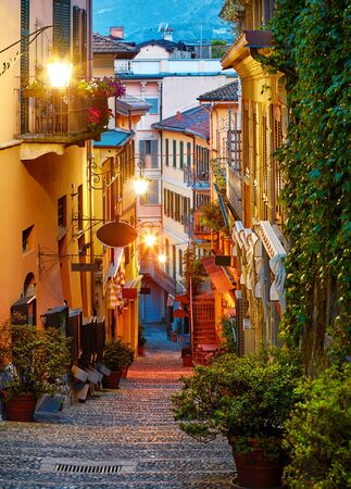 Bellagio village at lake Como near Milan Italy, region Lombardy. Famous street with paving stones stairs and cosy restaurants during sunrise with glowing lanterns and green plants on old houses walls Stockfoto