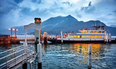 Bellagio village on lake Como, Italy. Ferryboat passenger transport by landing. Passengers ferry ship with arriving to the evening town. Evening time blue hour with dramatic sky and clouds.