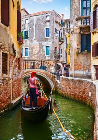 Gondolier in gondola Grand Canal in Venice, Italy.