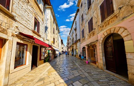 Croatia Porec. Central street old town paved stone paving stones with storefront shop in vintage house and windows with shutters. Sunny day and blue sky with white clouds. Reklamní fotografie