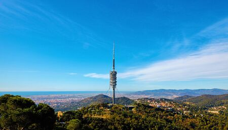 Barcelona Spain view from Mount Tibidabo of television tower and city. Scenic panorama with green hills and blue sky.